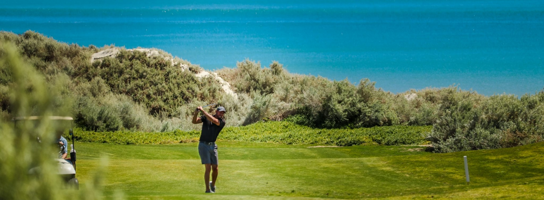 Man hits ball from the fairway with an ocean view in background